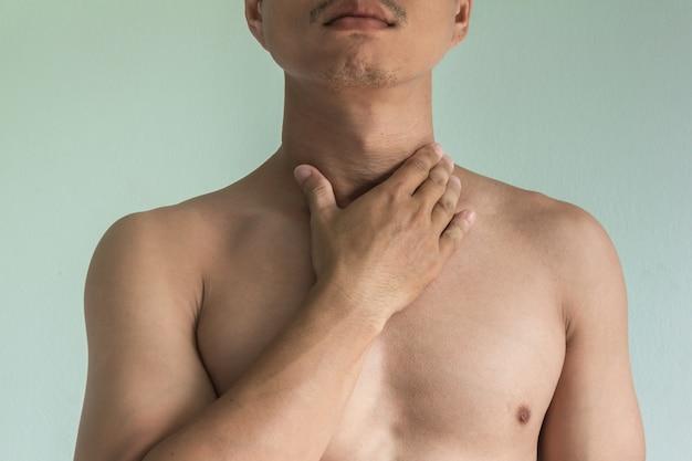 Homme asiatique avec maux de gorge