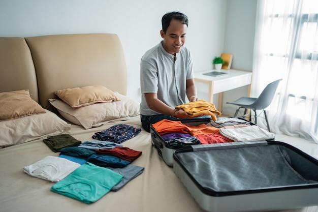 Homme asiatique mettant ses vêtements dans la valise