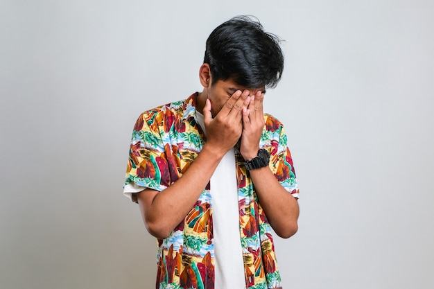 Homme asiatique avec moustache portant une chemise décontractée avec une expression triste couvrant le visage avec les mains en pleurant. concept de dépression sur fond blanc