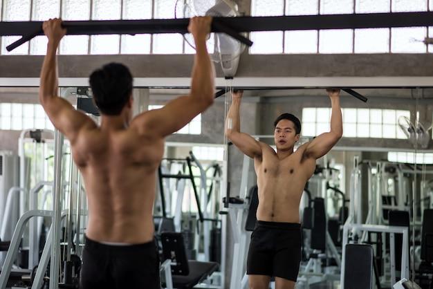 Homme asiatique musclé, barre haute, dans, gymnase