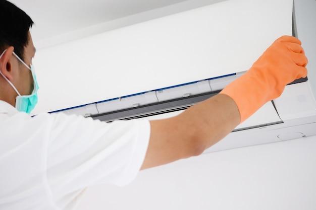 Homme asiatique nettoyage filtre sale du climatiseur