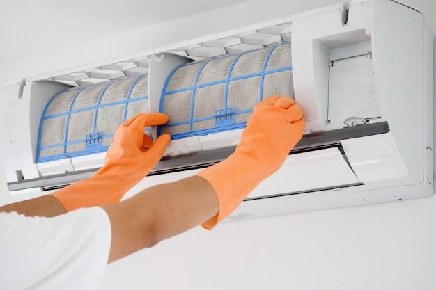 Homme asiatique nettoyant le filtre sale du climatiseur