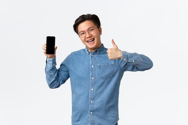 Homme asiatique optimiste et satisfait avec des bretelles portant des lunettes et des vêtements décontractés montrant le pouce dans l'application ...