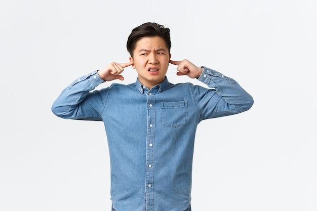 Homme asiatique perturbé et frustré se plaignant d'un bruit fort, ferme les oreilles et semble mécontent, fronçant les sourcils, disant au voisin de se taire, un étudiant ne peut pas se concentrer à cause de la musique horrible et bruyante.