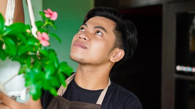 Homme asiatique, plantes suspendues à la maison font une belle décoration