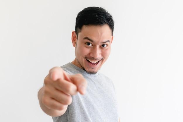 L'homme asiatique pointe vers la caméra avec une expression faciale excitée.