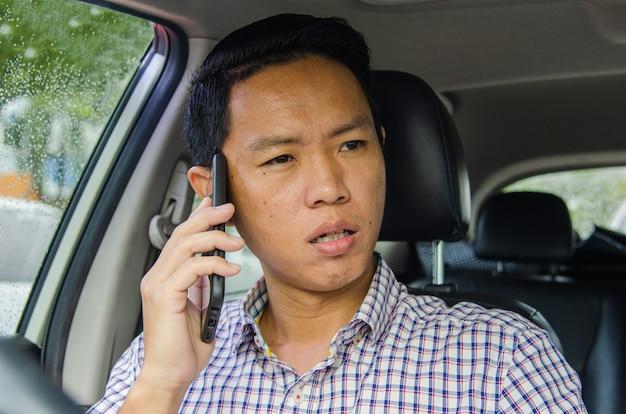 Homme asiatique portant une chemise à carreaux se penche sur un téléphone intelligent dans une voiture.