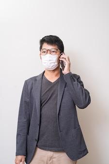 Homme asiatique portant un masque chirurgical pour prévenir la grippe coronavirus et à l'aide de téléphone portable