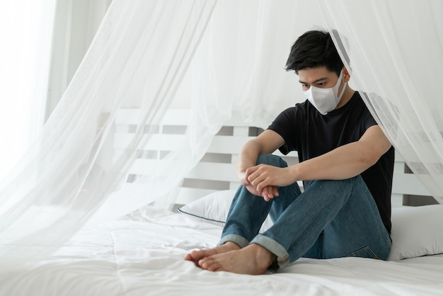 Homme Asiatique Portant Un Masque Facial Pour Se Protéger Des Maux De Tête Et De La Toux à Cause Du Coronavirus Covid-19 Dans La Salle De Quarantaine Photo gratuit