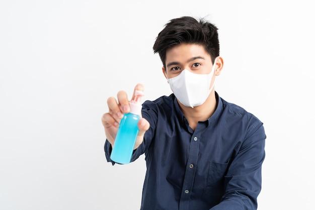 Homme Asiatique Portant Un Masque Facial Tenant De L'alcool Pour Se Laver Les Mains Pour Protéger Le Coronavirus Covid-19 Dans La Salle De Quarantaine Photo gratuit