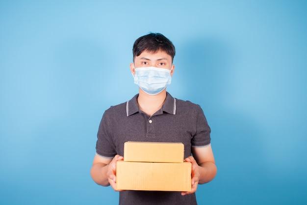 Un homme asiatique portant un masque livre des boîtes de livraison express sur fond bleu