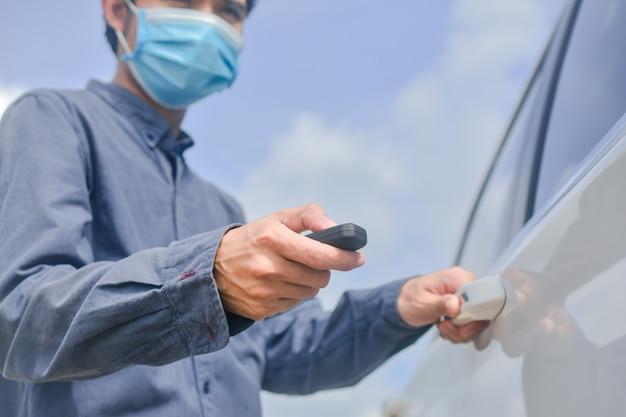 Homme asiatique portant un masque médical et tenant la clé pour ouvrir la porte de la voiture
