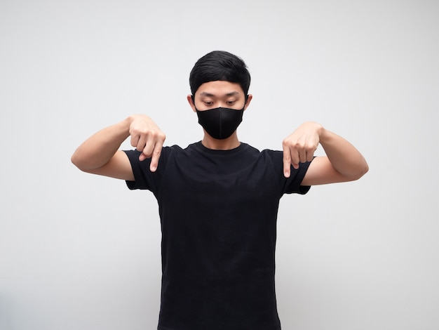 Un homme asiatique portant un masque pointe le double doigt et regarde vers le bas sur fond blanc