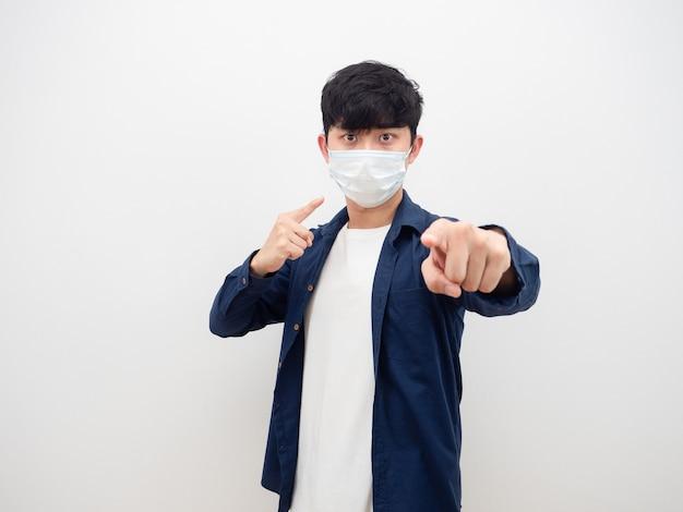 Homme asiatique portant un masque serius visage pointer le doigt athis face et vous pointer sur fond blanc