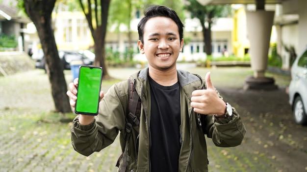 Homme asiatique portant un téléphone portable à écran vert avec un geste ok
