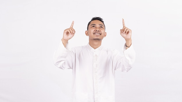Homme asiatique portant des vêtements musulmans pointant un écran blanc isolé espace blanc
