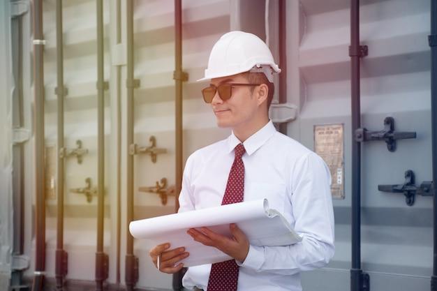 Un homme asiatique porte une chemise blanche et une cravate rouge et un chapeau de sécurité blanc travaille sur un chantier de construction.