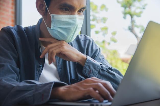 Un homme asiatique porte un ordinateur de travail à la maison avec un masque facial, commerce en ligne à la maison