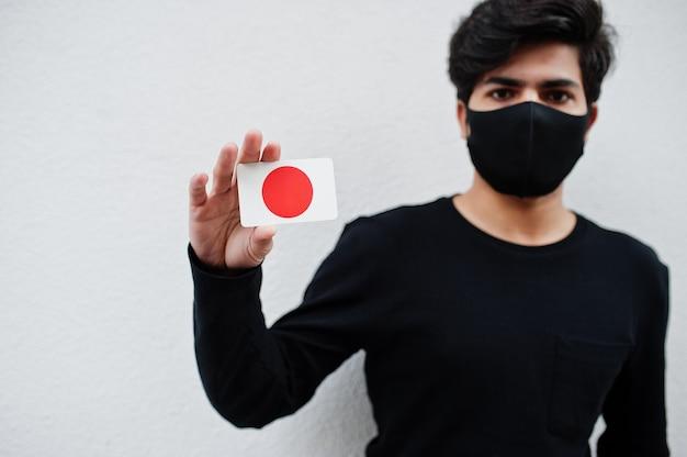 Homme asiatique porter tout noir avec masque facial tenir le drapeau du japon à la main isolé sur blanc. concept de pays de coronavirus.