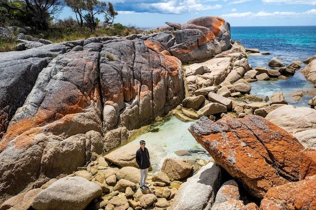 Un homme asiatique pose pour la caméra en se tenant debout sur de gros rochers à côté d'une mer