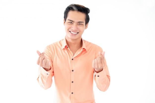 Homme asiatique positif qui montre un geste pour de l'argent
