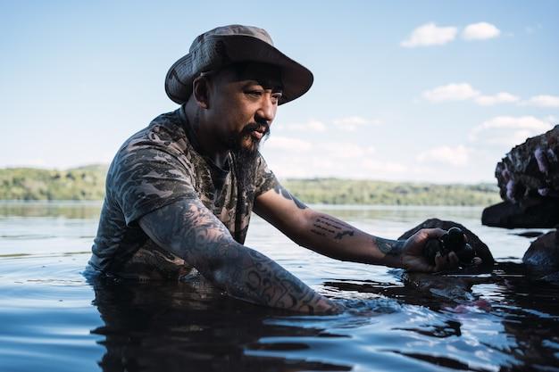 Homme asiatique ramassant des escargots dans la rivière