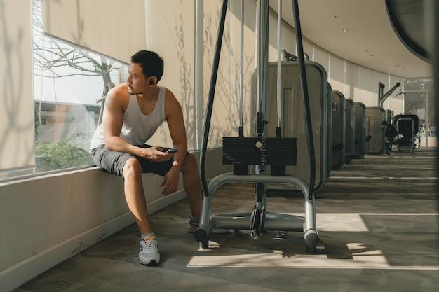Homme asiatique reste entre ensemble de formation d'entraînement dans la salle de gym.