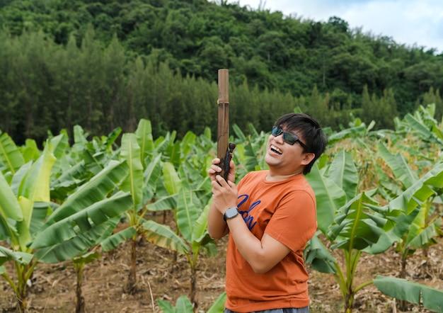 Homme asiatique riant de bonheur tenant un bang en bambou fumant dans une ferme de bananiers sur une colline verte