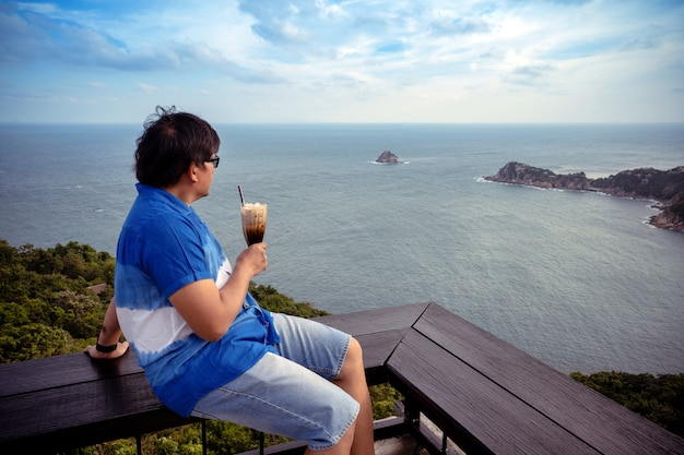 Un homme asiatique s'assoit au point de vue supérieur se détend et regarde la côte de la mer tenant un café au lait glacé