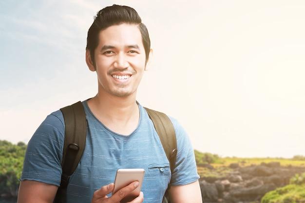 Homme asiatique avec un sac à dos tenant un smartphone avec vue sur le lac et ciel bleu. journée mondiale du tourisme