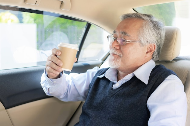 Un homme asiatique senior se sent heureux de boire du café chaud, un latte chaud, un cappuccino chaud dans sa voiture - concept de bonheur senior de style de vie