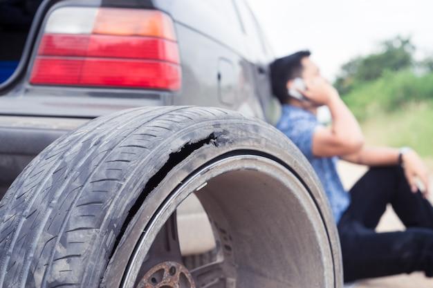 Un homme asiatique sérieux appelle un smartphone parce que la roue est cassée