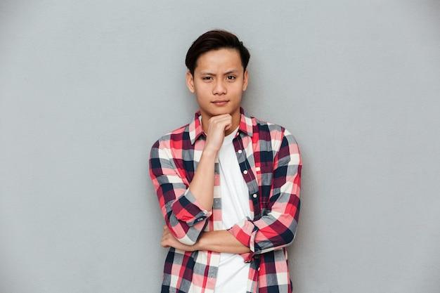 Homme asiatique sérieux debout sur un mur gris.