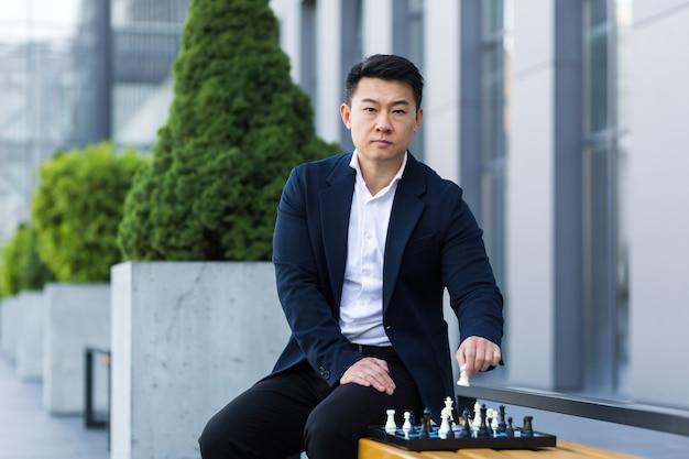 Homme asiatique sérieux jouant aux échecs à l'extérieur, homme d'affaires pensant jouer aux échecs assis sur un banc près du centre de bureaux