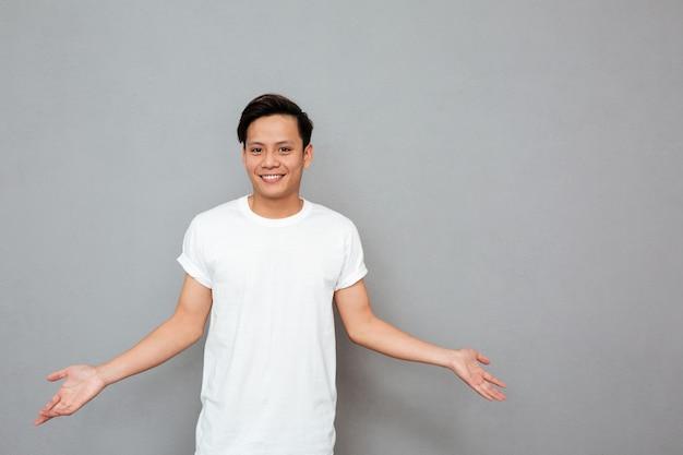 Homme asiatique souriant, debout sur un mur gris.