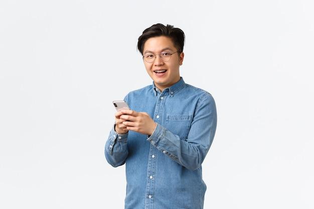 Homme asiatique souriant et divertissant avec des bretelles, portant des lunettes, des messages ou regardant des vidéos sur internet, utilisant une application pour téléphone portable, regardant la caméra avec plaisir, debout sur fond blanc