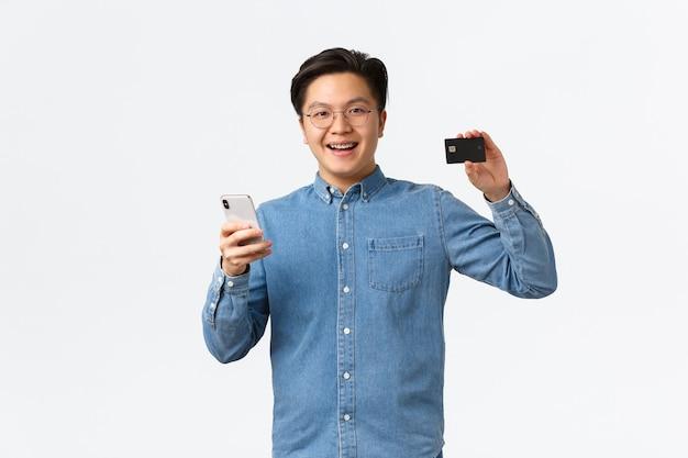 Un homme asiatique souriant et heureux dans des lunettes et des vêtements décontractés utilisant un téléphone portable pour transférer de l'argent sur un compte bancaire, montrant une carte de crédit avec une expression satisfaite, debout sur fond blanc heureux.