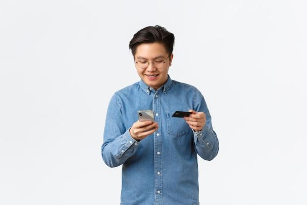 Un homme asiatique souriant et heureux dans des verres payant des services en ligne avec une carte de crédit, envoyant de l'argent à un compte ami, tenant un smartphone et regardant un écran mobile satisfait, fond blanc.