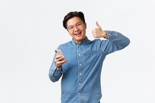 Homme asiatique souriant heureux et satisfait avec des bretelles et des lunettes montrant le pouce levé heureux après avoir essayé d'utiliser une nouvelle application, tenant un téléphone portable, laissant des commentaires positifs sur l'application, fond blanc.