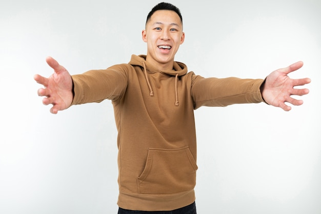 Homme asiatique en sweat à capuche marron à bras ouverts