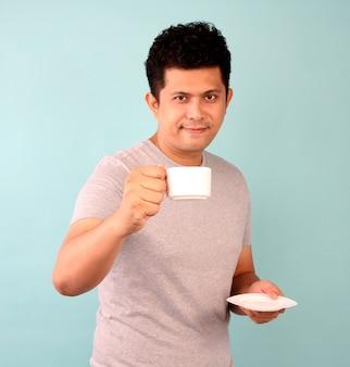 Un homme asiatique en t-shirt gris boit une tasse de café, thé sur un bleu.