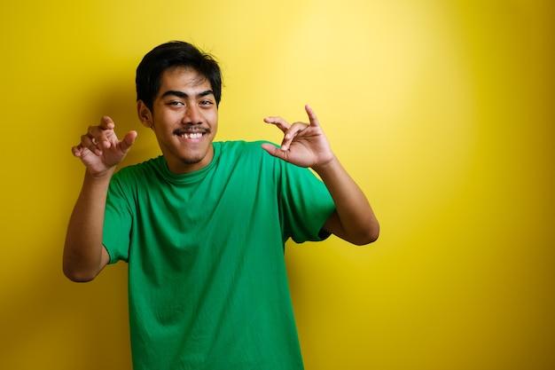 Homme asiatique en t-shirt vert souriant et dansant joyeusement, joyeux exprimant la célébration de la bonne nouvelle, la victoire remportant le geste de réussite sur fond jaune