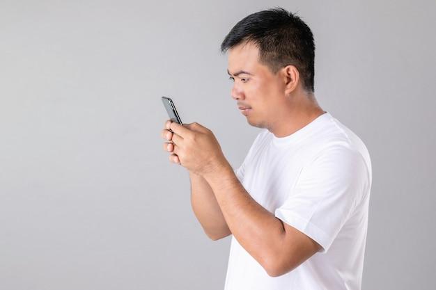 Homme asiatique tapant ou bavardant sur smartphone