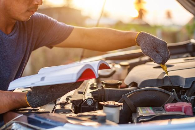 Homme asiatique tenant et lisant le manuel d'utilisation de la voiture pour vérifier le moteur de la voiture moderne