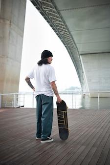 Homme asiatique tenant sa planche à roulettes