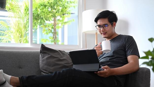 Homme asiatique tenant une tasse de café et utilisant une tablette informatique sur un canapé.