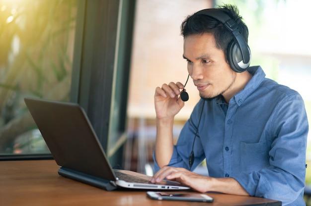 Un homme asiatique travaillant un centre d'appels en ligne indépendant au café