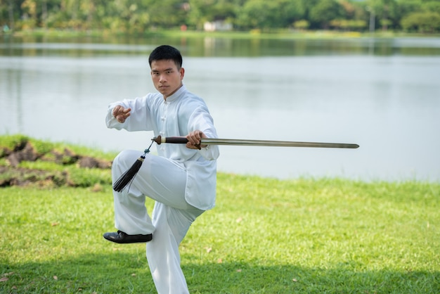 Homme asiatique travaillant avec une épée de tai chi le matin au parc, arts martiaux chinois, concept de soins de santé pour la vie.
