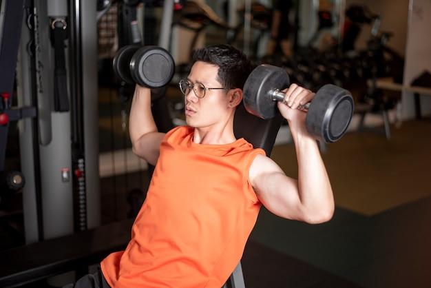 Homme asiatique travaille dans la salle de gym