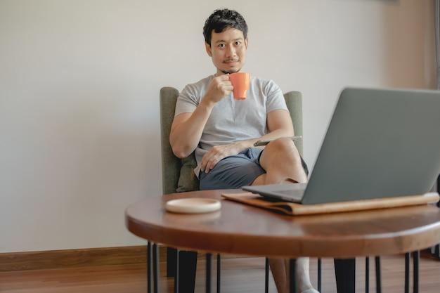 L'homme asiatique travaille avec son ordinateur portable et boit du café.